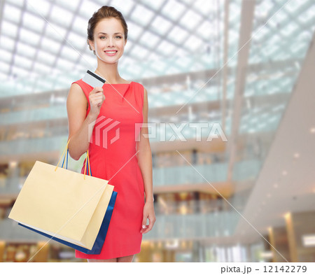 smiling woman with shopping bags and plastic cardの写真素材 [12142279] - PIXTA