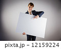 Smiling businesswoman holding and pointing to poster 12159224