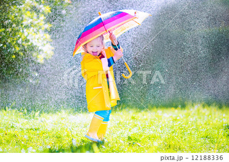 Funny little toddler with umbrella playing in the rain 12188336