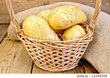 Potatoes yellow in basket with burlap on boardの写真素材 [12499306] - PIXTA