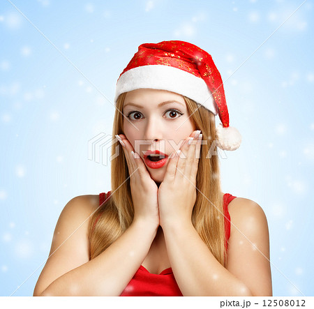 Young woman in santa hat surprised 12508012