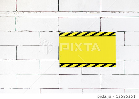 cement block wall with blank warning poster template to fill youの