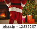 Mid section of santa standing in front of the christmas tree 12839267