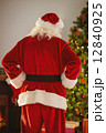 Rear view of santa standing in front of the christmas tree 12840925