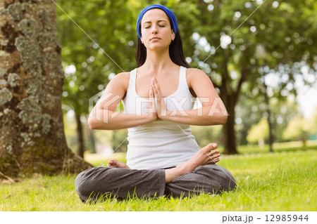 brunette sitting in lotus pose with hands togetherの写真素材