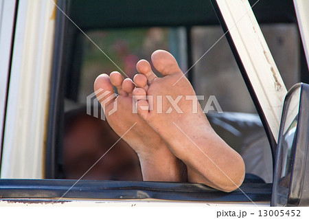 The driver sleeps legs sticking out the car window 13005452