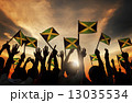 Group of People Waving Flag of Jamaica in Back Lit 13035534