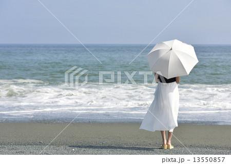 海辺で日傘をさす女性の後ろ姿 13550857