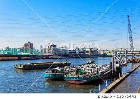 青空が広がる隅田川を行き来する船舶と給油作業中のタンカー 13575443