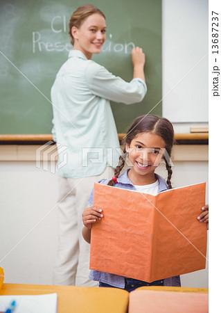 Cute pupil smiling at camera during class presentationの写真素材 [13687237] - PIXTA