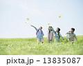 草原で紙飛行機を飛ばす小学生 13835087
