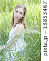 Photo of young blonde woman sitting in the green grass and looki 13853467
