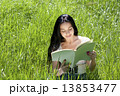 Photo of young attractive brunette woman sitting on grass and re 13853477