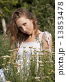 Photo of young blonde woman sitting near achillea bushes 13853478