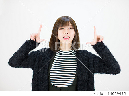 両手の人差し指で上を指す笑顔の若い女性 14099436