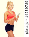 smiling sporty woman with smartphone and earphones 14239789