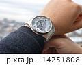 世界時計を着けようとしている男性の腕 14251808