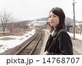駅のホームで電車を待つ若い女性 14768707