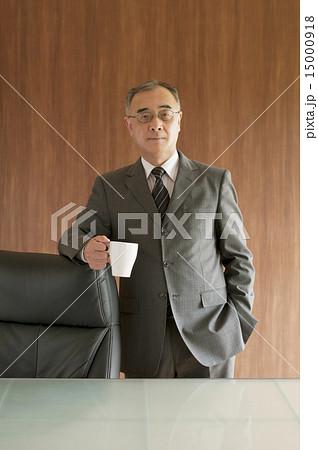コーヒーカップを持ち椅子に寄りかかるビジネスマンの写真素材