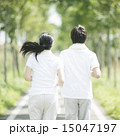 一本道でジョギングをするカップルの後姿 15047197