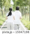 一本道でジョギングをするカップルの後姿 15047198