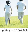 草原でジョギングをするカップルの後姿 15047321