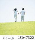 草原でジョギングをするカップルの後姿 15047322