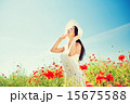 smiling young woman in straw hat on poppy field 15675588