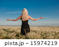 The girl in a black dress standing in the grain field arms sprea 15974219
