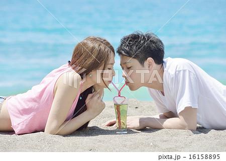 ビーチで寄り添いハート型のストローでドリンクを飲むカップル 16158895