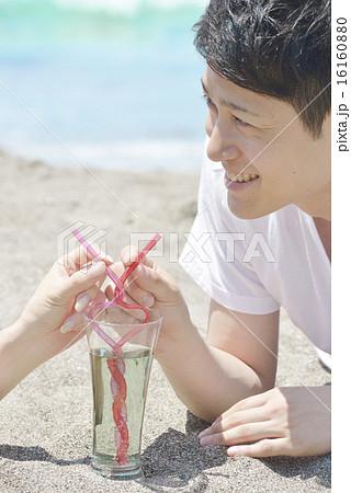 ビーチで寄り添いハート型のストローでドリンクを飲むカップル 16160880