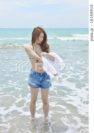 ビーチで着替えする若い女性 16168919