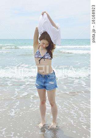 ビーチで着替えする若い女性 16168923