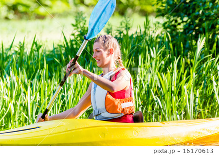 Woman paddling with canoe on forest river 16170613