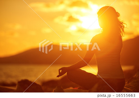 woman meditating in lotus pose on the beach at sunsetの写真素材