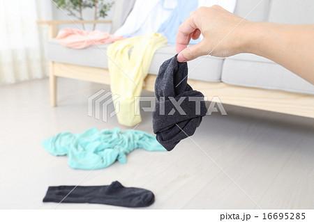 脱ぎ散らかした服・汚い靴下をつまむ手 16695285