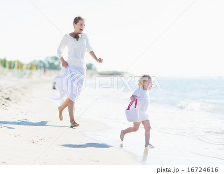 Happy mother and baby playing on sea coast