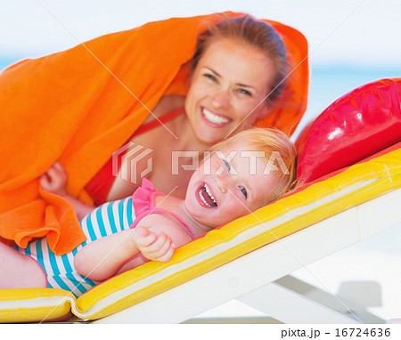 Portrait of happy mother and baby laying on chaise-longue