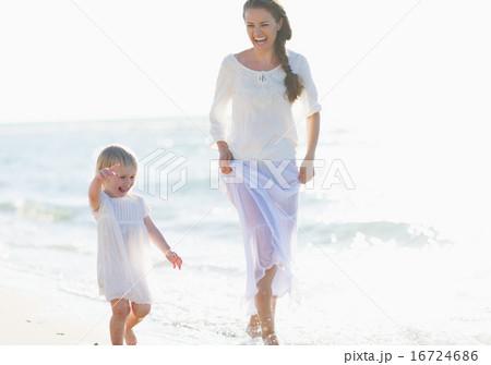 Happy mother and baby walking along sea coast
