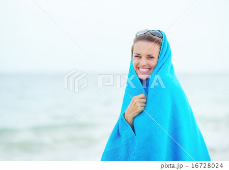 Portrait of happy young woman in towel at seaside 16728024