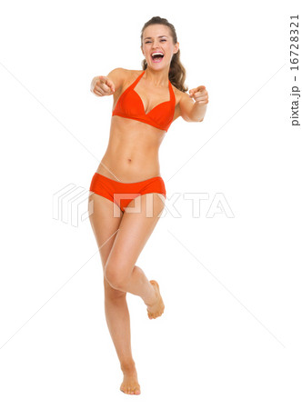 Full length portrait of smiling young woman in swimsuit pointing