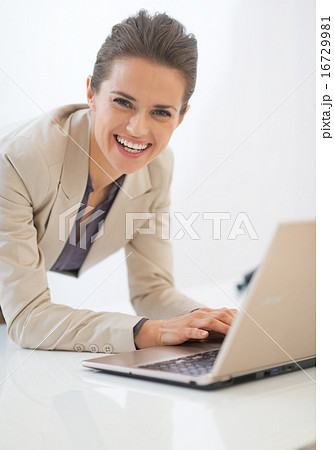 Smiling business woman working on laptop in office
