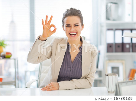 Portrait of smiling business woman showing ok gesture in office
