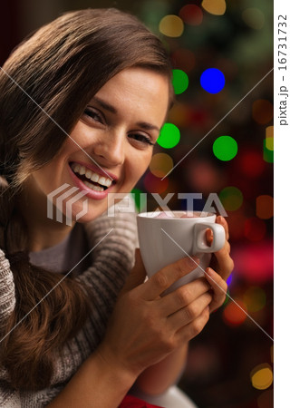 Happy young woman enjoying cup of hot chocolate in front of Chri