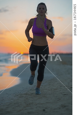 Fitness young woman running on beach at dusk