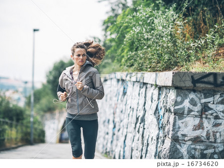 Fitness young woman jogging in the city park