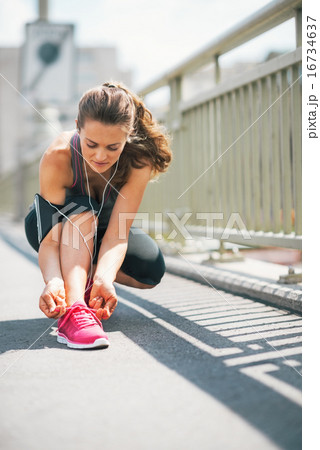 Fitness young woman tying shoelaces in the city