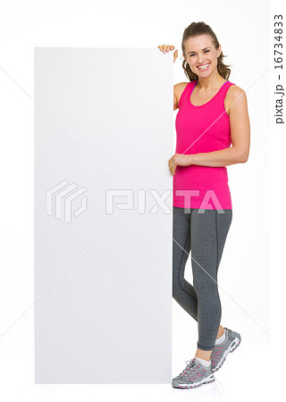 Smiling fitness young woman showing blank billboard