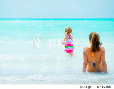 Mother and baby girl relaxing at seaside. rear view