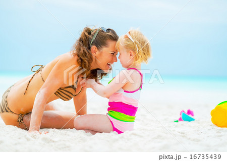 Portrait of smiling mother and baby girl playing on beach